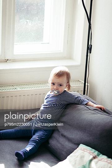Junge sitzt auf Sofa und entspannt - p795m2230051 von JanJasperKlein