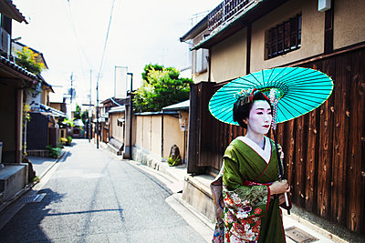 A woman dressed in the traditional geisha style, wearing a kimono and obi, with an elaborate hairstyle and floral hair clips, with white face makeup with bright red lips and dark eyes holding a paper parasol walking along a street.  - p1100m1185750 by Mint Images
