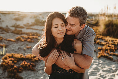 Mid-40's husband embraces beautiful wife with sand dune in background - p1166m2207839 by Cavan Images