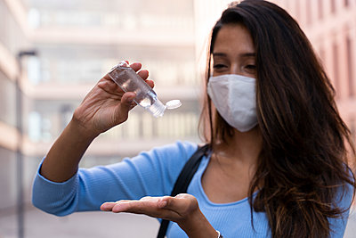Businesswoman in face mask pouring sanitizer on hand during COVID-19 - p300m2224930 by VITTA GALLERY