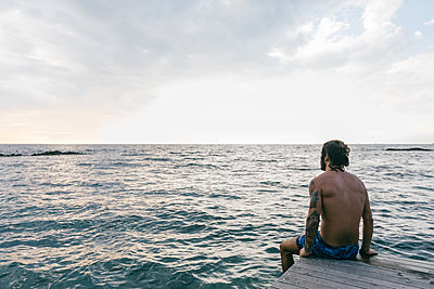 Man sitting on edge of sea - p429m2202356 by Sofie Delauw
