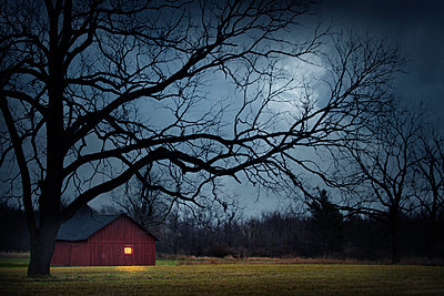 Illuminated barn in rural landscape - p555m1454190 by Chris Clor