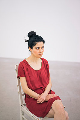 Woman in red dress sits on chair - p586m1034885 by Kniel Synnatzschke