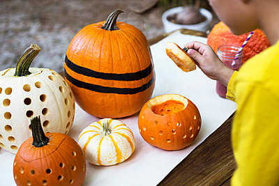 Over shoulder view of boy lifting pumpkin lid on garden table - p924m1468782 by Kinzie Riehm