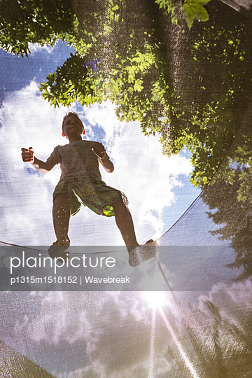 Boy standing on net in playground on a sunny day - p1315m1518152 by Wavebreak