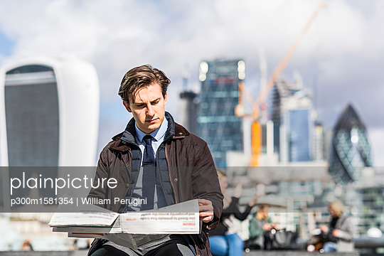 UK, London, portrait of serious businessman reading newspaper - p300m1581354 von William Perugini