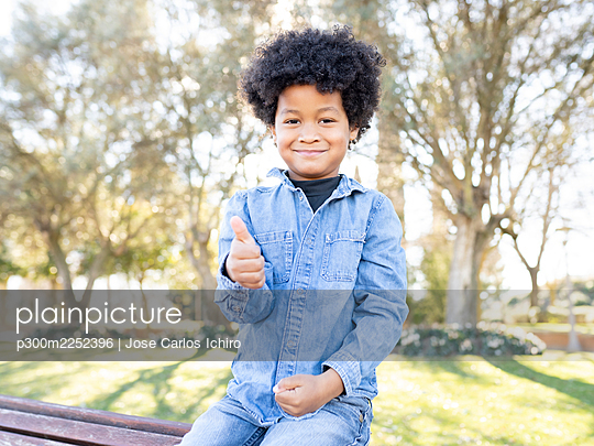 Smiling boy showing thumbs up while sitting at park - p300m2252396 by Jose Carlos Ichiro
