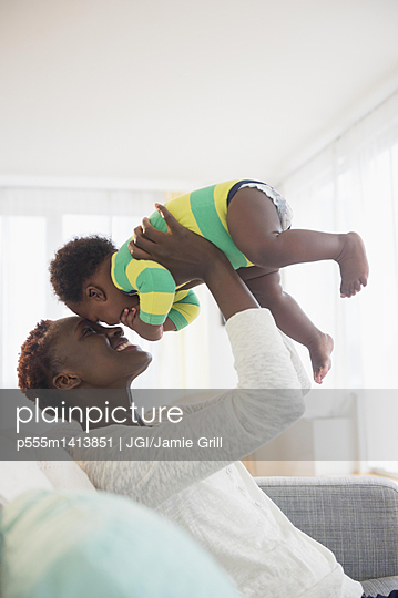 Black mother playing with baby boy on sofa - p555m1413851 by JGI/Jamie Grill