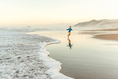 Preschool boy running in water at a beach - p1166m2129637 by Cavan Images