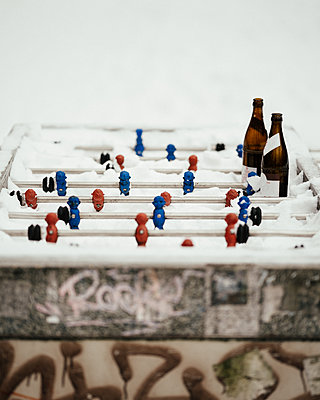 Snowcapped tabletop football with beer bottles - p1549m2245180 by Sam Green