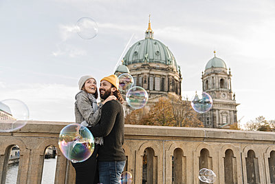 Happy young couple embracing watching soap bubbles in the city, Berlin, Germany - p300m2154540 von Hernandez and Sorokina