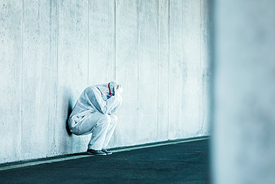 Despaired man wearing protective clothing leaning against concrete wall - p300m2171390 by Valentin Weinhäupl