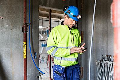 Builder using cell phone - p312m1187681 by Susanne Kronholm