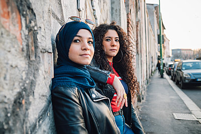 Young woman in hijab and best friend leaning against wall on city sidewalk - p429m2127752 by Eugenio Marongiu