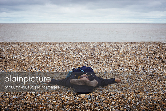 Woman lying on her back on a pebble beach by the ocean. - p1100m1490131 by Mint Images