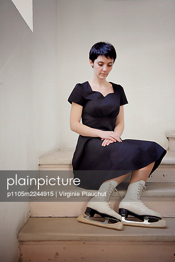 Woman in black dress and skates in the stairwell - p1105m2244915 by Virginie Plauchut