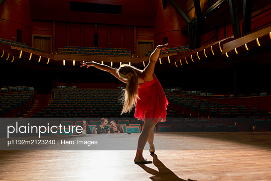 Female dancer performing for judges on stage in auditorium - p1192m2123240 by Hero Images