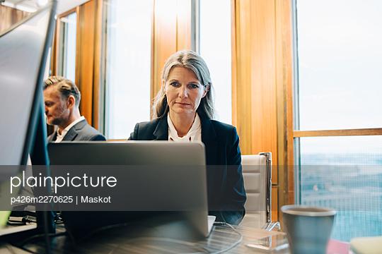 Female lawyer walking on laptop in office - p426m2270625 by Maskot