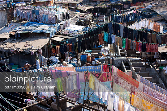 Indian hand laundry, Dhobi Ghat, and laundrymen with traditional flogging stones to wash clothing at Mahalaxmi, Mumbai, India - p871m895801 by Tim Graham