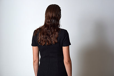 Rear view of a woman in black facing a white wall - p1096m2063930 by Rajkumar Singh
