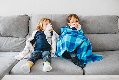 Little girl and her brother sitting side by side on the couch at home blowing noses - p300m2180868 by Josep Rovirosa