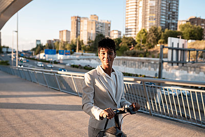 Businesswoman with electric scooter standing on footbridge in city - p300m2290547 by Jose Carlos Ichiro
