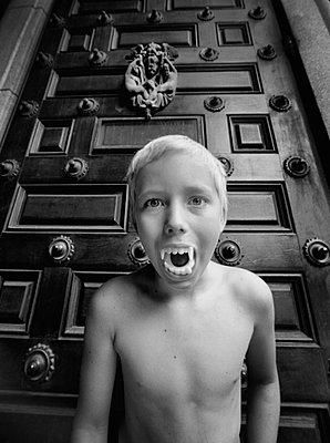Portrait of boy wearing vampire teeth - p312m764827 by Bruno Ehrs