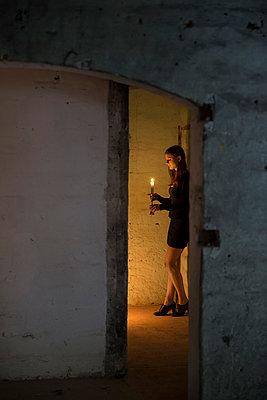 Frau mit Kerze in einem Keller - p335m1041639 von Andreas Körner
