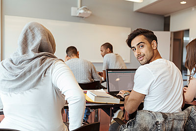 Portrait of smiling man using laptop while sitting with friends in classroom - p426m2072232 by Kentaroo Tryman