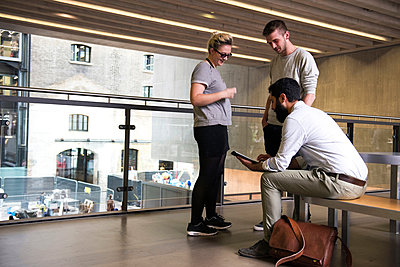 Man with colleagues on mezzanine in office building using digital tablet - p429m1513879 by G. Mazzarini