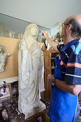Sculptor admiring wood figure - p429m747167f by Stefano Gilera