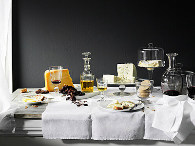 Wine, cheese and bread on table - p429m756389 by Brett Stevens