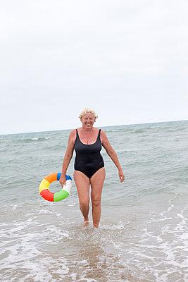 Ältere Frau mit Schwimmreifen  - p505m1195410 von Iris Wolf