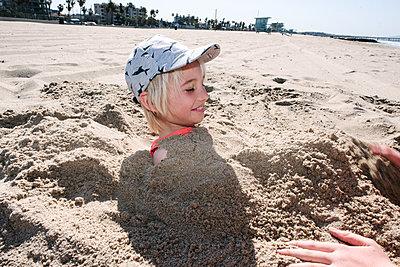 Boy being buried in sand on beach - p924m2271145 by Viara Mileva