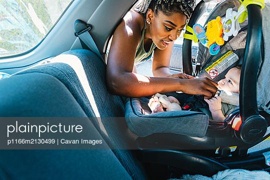 Mother buckling her baby girl in car seat - p1166m2130499 by Cavan Images