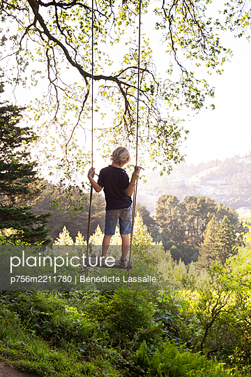 Boy on a swing in the countryside, California - p756m2211780 by Bénédicte Lassalle