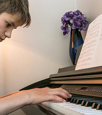 Boy playing piano - p1082m2015488 by Daniel Allan