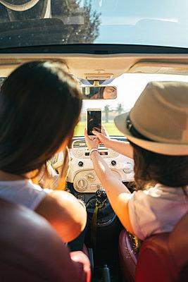 Two women in car taking a selfie - p1165m1222155 by Pierro Luca