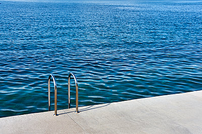 Pool ladder on the shore of the slovenian adriatic coast, Piran, Slovenia, 2017 - p1362m1584088 by Charles Knox