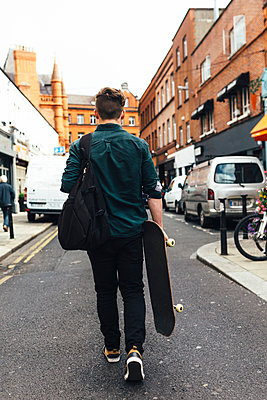 Ireland, Dublin, back view of young man with skateboard walking on the street - p300m1189086 by Boy photography