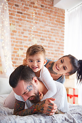 Happy family playing at Christmas time in bed - p300m2041664 by gpointstudio