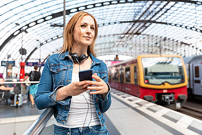 Smiling woman with smartphone and headphones on the station platform, Berlin, Germany - p300m2156836 by William Perugini