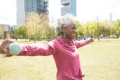 Smiling senior woman with arms outstretched holding dumbbells in public park - p300m2290737 by Pete Muller