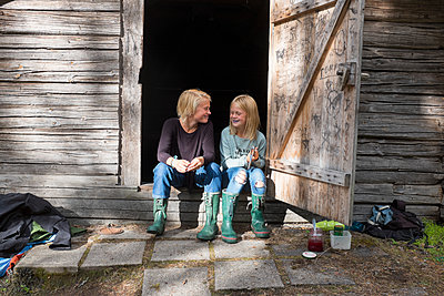 Girl and teenage boy sitting in front of barn - p312m1338599 by Johan Willner