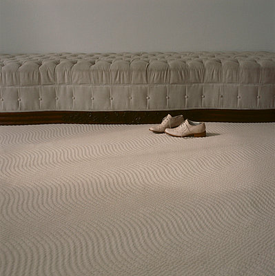 Pair of men's shoes next to a upholstered sofa in a neutral coloured carpeted living room - p349m695199 by Emma Lee