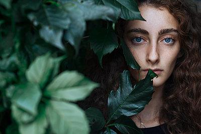 Portrait of serious Caucasian woman behind leaves - p555m1531632 by Ivan Ozerov