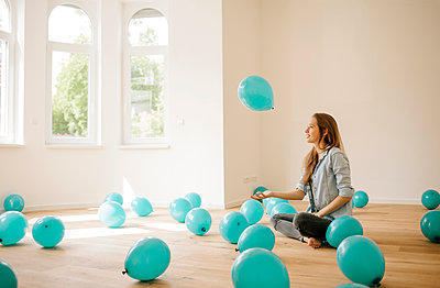 Young woman in new apartment playing with balloons - p586m1064882 by Kniel Synnatzschke