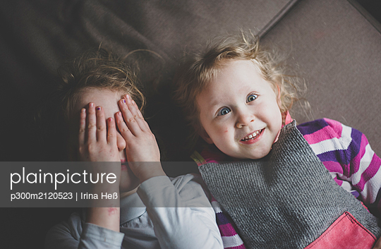 Portrait of two little sisters lying on couch having fun, top view - p300m2120523 by Irina Heß
