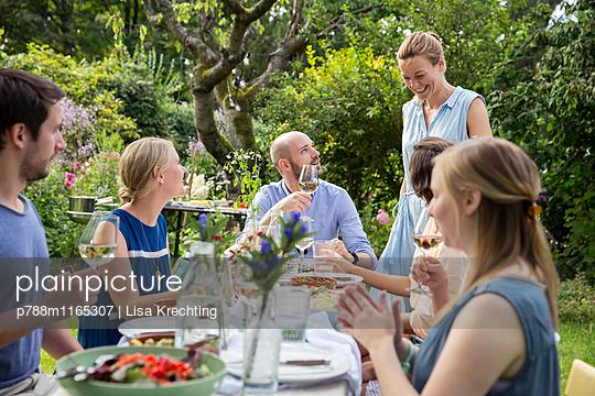 Freunde feiern eine Gartenparty - p788m1165307 von Lisa Krechting