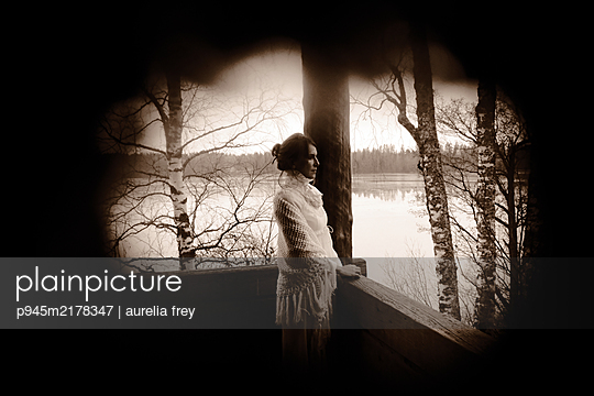 Woman on balcony looking out onto lake - p945m2178347 by aurelia frey